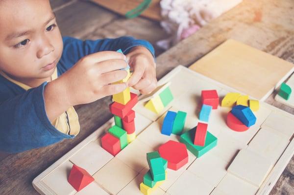 nino-aprendiendo-construccion-bloques-madera-color_38335-62